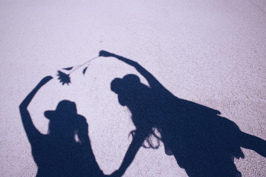 太陽の下、自分たちの影で遊ぶ双子の女の子たち