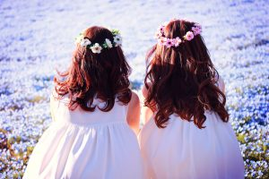 ふたり並んで花畑を見つめる双子の女の子たち