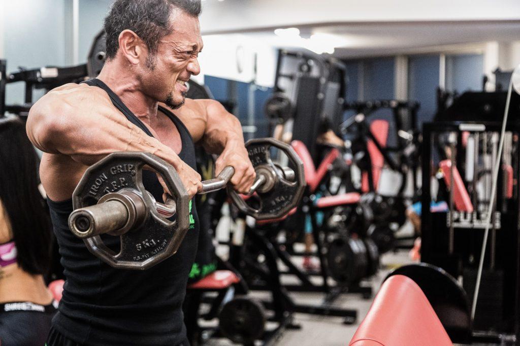 バーベルで筋肉に負荷をかけるボディビルダー
