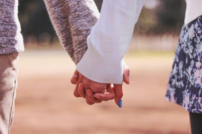 公園で仲良く手をつなぐ付き合いたてのカップルのフリー写真画像