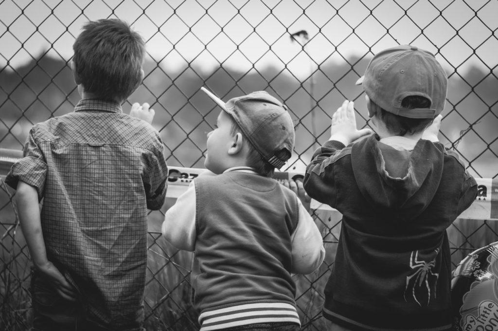 フェンスの向こうを見ている少年たち