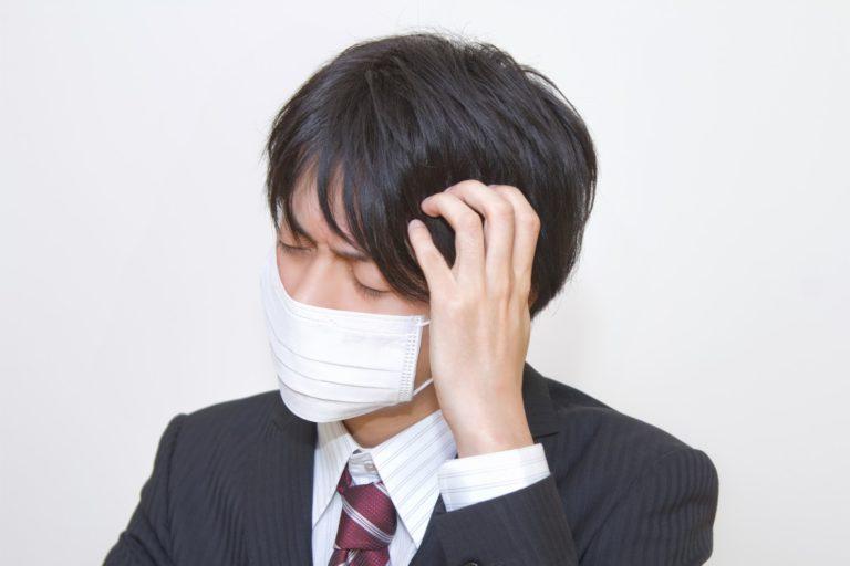 マスクをして頭をかかえるスーツの男性