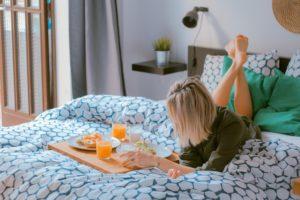 ベッドで朝食を食べる女性