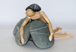 石に押しつぶされた人形